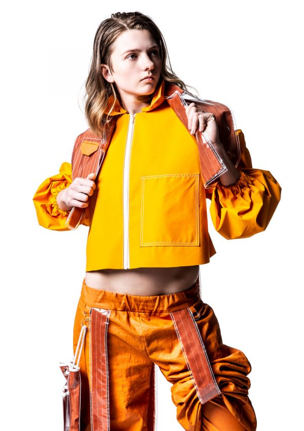 Megan Grinham - White female model wearing a jacket, crop top and cargo trousers in different shades of bright orange. The outfit is inspired by construction workers and is designed by BA Fashion student Megan Grinham