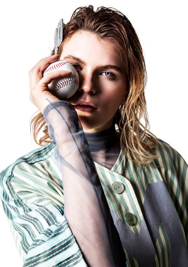 Molly Mackie - White female model is wearing a baseball style yellow/green/grey striped shirt, with a mint green M on the front, looking directly into camera. Under the shirt she is wearing a greay mesh long sleeved tshirt. She holds a baseball up, covering her right eye. Garment designed by BA Fashion student Molly Mackie