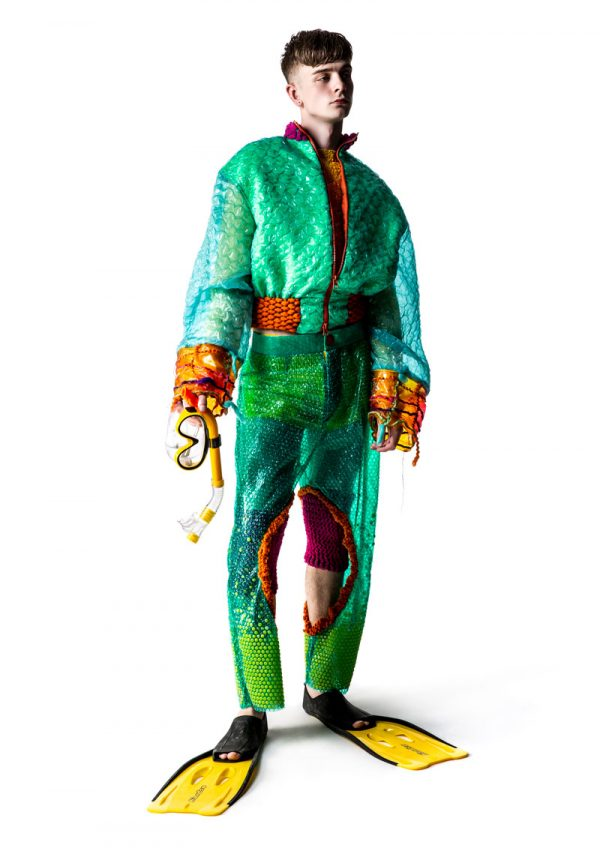 Phoebe Constable - White male model wearing a green and orange jacket and trousers with splits made from bioplastics; the trousers look similar to bubble wrap. Under the trousers are pink knitted shorts. The model wears yellow flippers for shoes and is holding goggles. Garment designed by BA Fashion student Phoebe Constable