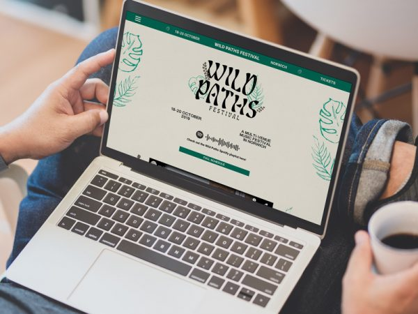 Jamie Greengrass - Website design for Wild Paths music festival in Norwich, by BA Graphic Communication student Jamie Greengrass. A person has a laptop open on a cream and green coloured website saying 'Wild Paths' with links to the full lineup.