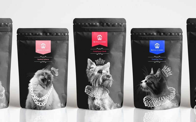 Packaging and branding design for Royal Canin pet foot by BA Graphic Design graduate Tom Hardwick. Three black pet food sachets stand in a row. On the left, a fluffy cat wears and illustrated white crown and jewelled necklace, in the middle a small dog wears a white crown and neck ruffles, and on the right, a black and white cat wears a white crown and neck ruffles. Each flavour has a different colour label.