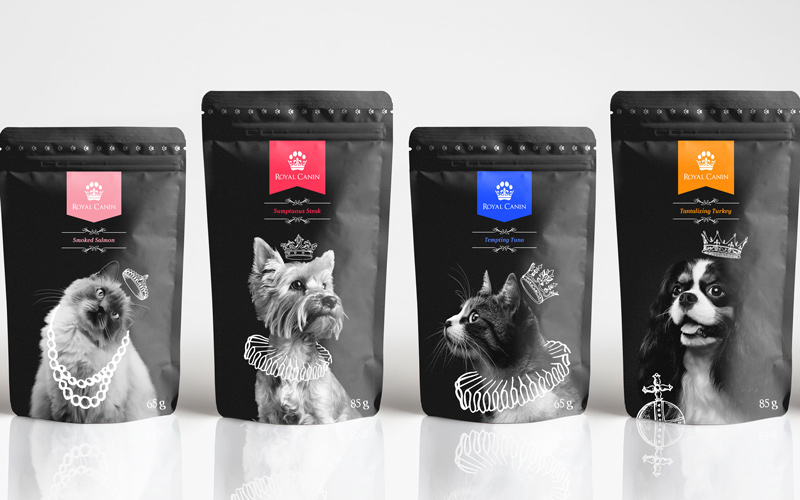 Packaging and branding design for Royal Canin pet foot by BA Graphic Design graduate Tom Hardwick. Four black pet food sachets stand in a row. On the sachets are photos of cats and dogs wearing illustrated royal accessories, such as crowns, jewels and neck ruffles. Each flavour has a different colour label.