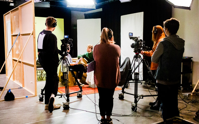 NUA students working with camera equipment on a makeshift set in the Sir John Hurt studio on campus