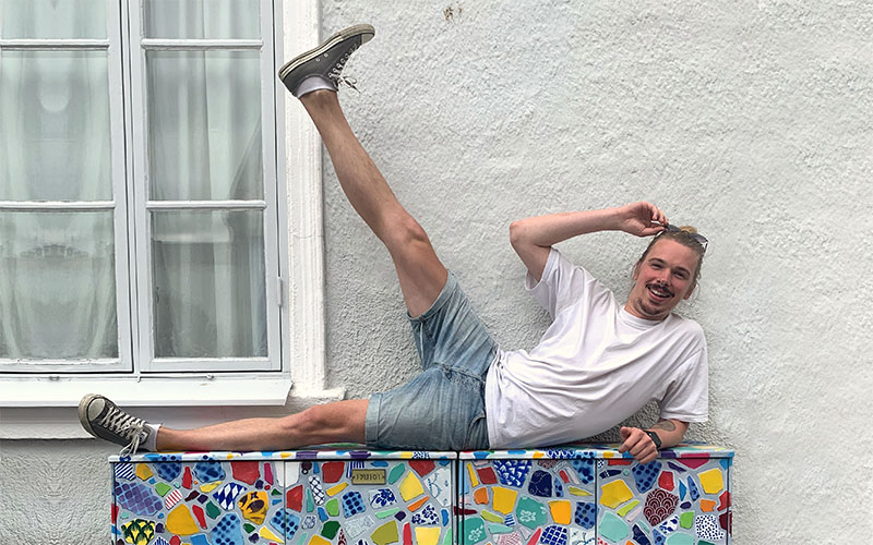 BA Animation student August Abrahamsson lying on a bench with one leg in the air