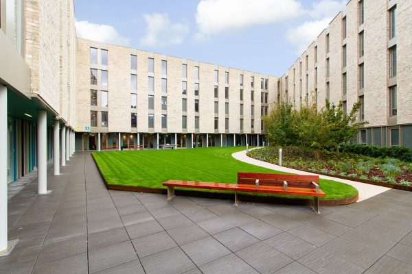 Communal courtyard - Courtyard at Benedicts Gate Norwich, showing grass, bench and a building