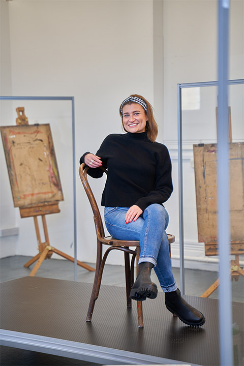Claire allergen sitting on wooden chair with legs crossed and one arm on the back of chair on black platform. Claire has jeans and black jumper on. 2 artist easels in background.