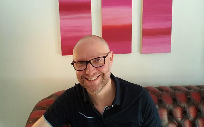 Portrait of Games Development lecturer Harry Holmwood sat on a sofa