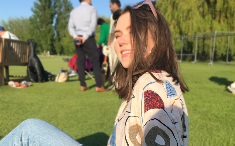 BA Graphic Design student Olivia Knights, sitting on grass at a park in the sunshine