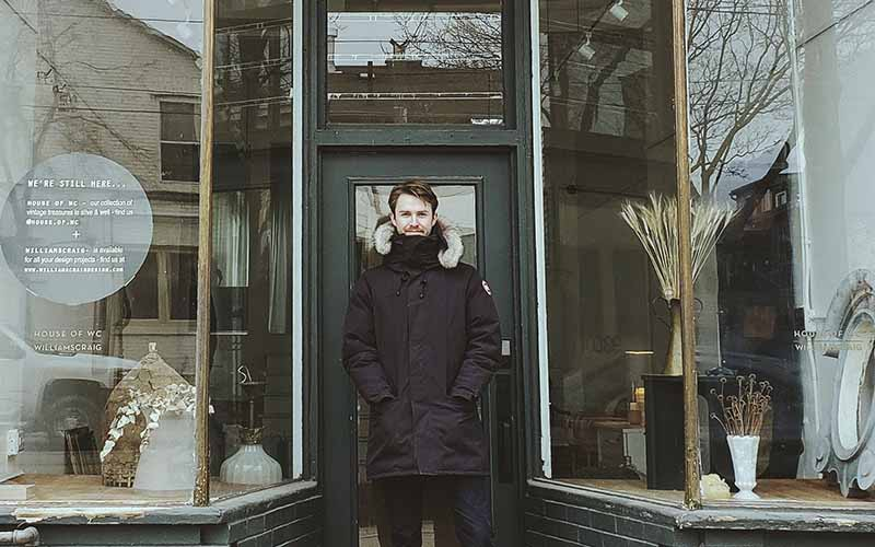A man in a black coat and face mask stood in the doorway of a building between two big bay windows