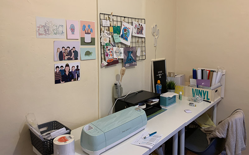 student home studio with desk with box of vinyl and vinyl printer with various drawings on the wall