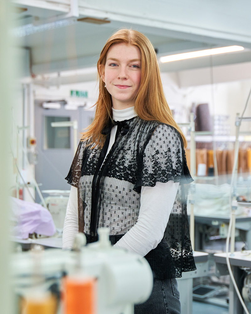 Photo of a young red haired woman standing amongst sewing machines in a fashion studio, looking into camera