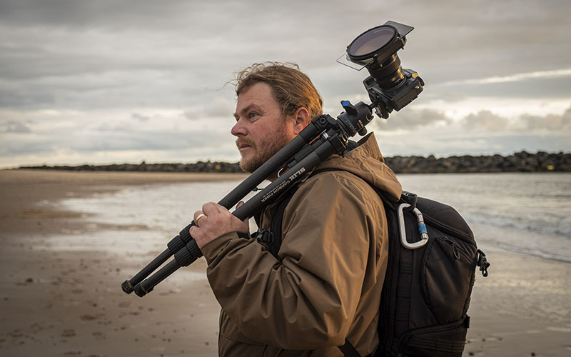 A man standing on a sandy beach with a black backpack and a tripod over his shoulder