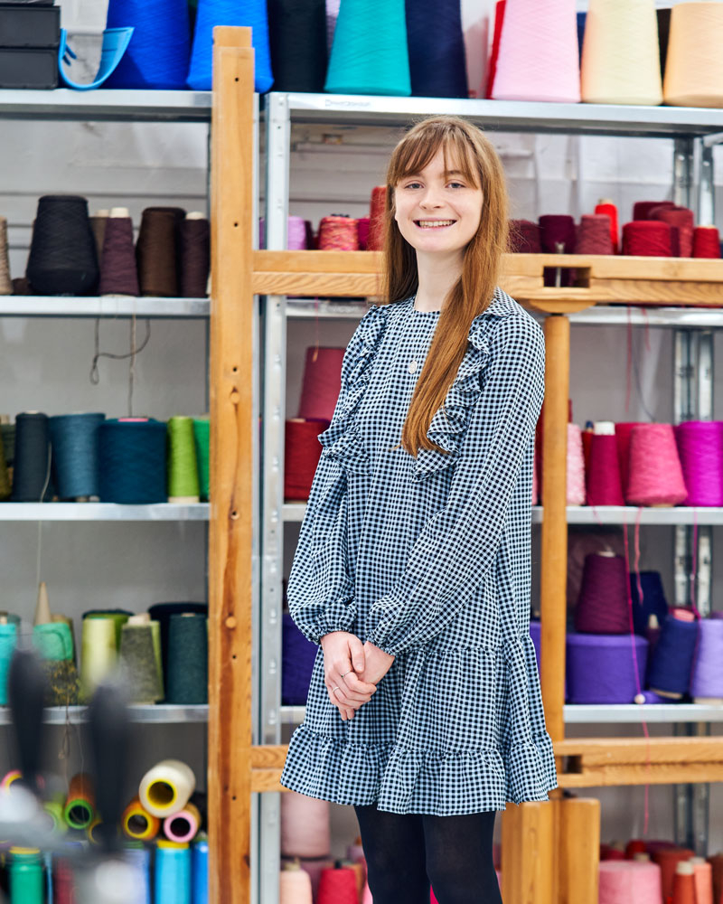 Photograph of a young woman with long hair, standing in the Textile Design workshop in front of multicoloured yarn and thread