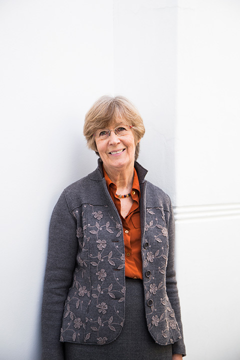 Professor Marcia Pointon standing against a wall at Norwich University of the Arts wearing a jacket