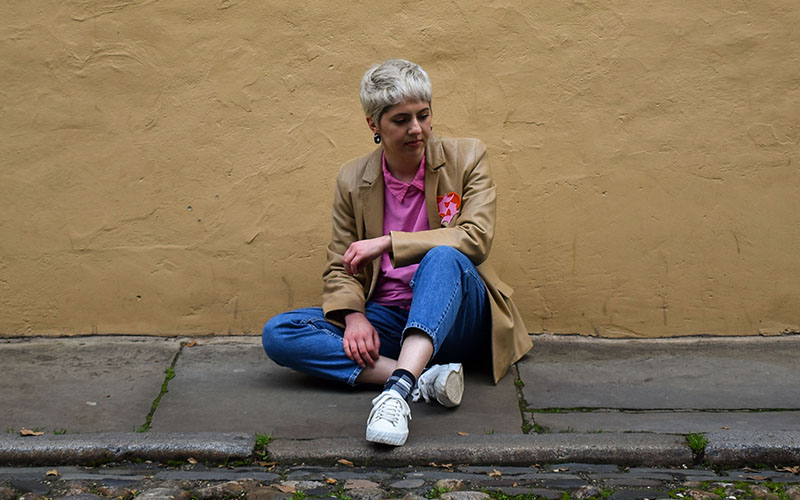 Young person with cropped blonde hair and blue jeans sitting on the pavement in front of a dark yellow wall