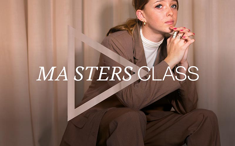 A woman in a brown suit resting her chin in her hands against beige curtains, with the words Masters Class on top
