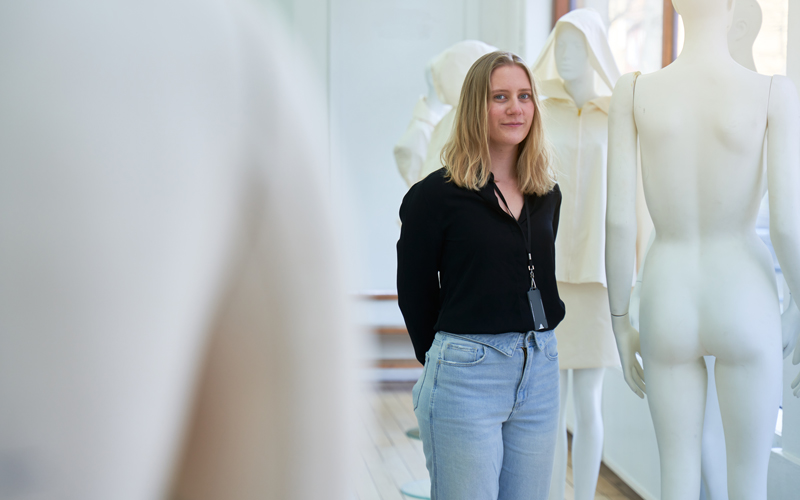 A young woman with mid-length dirty-blonde hair, standing amongst mannequins in the fashion studio looking at the camera