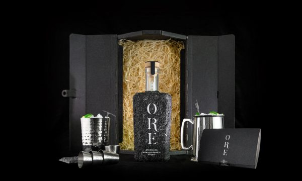 Tom Hardwick - Packaging for non alcoholic drink 'Ore'. A metal miners box is filled with shredded tissue, with the bottle of spirit in front. The bottle is made of hard black ore. Two metal tankards are either side of the bottle, with promotional leaflets