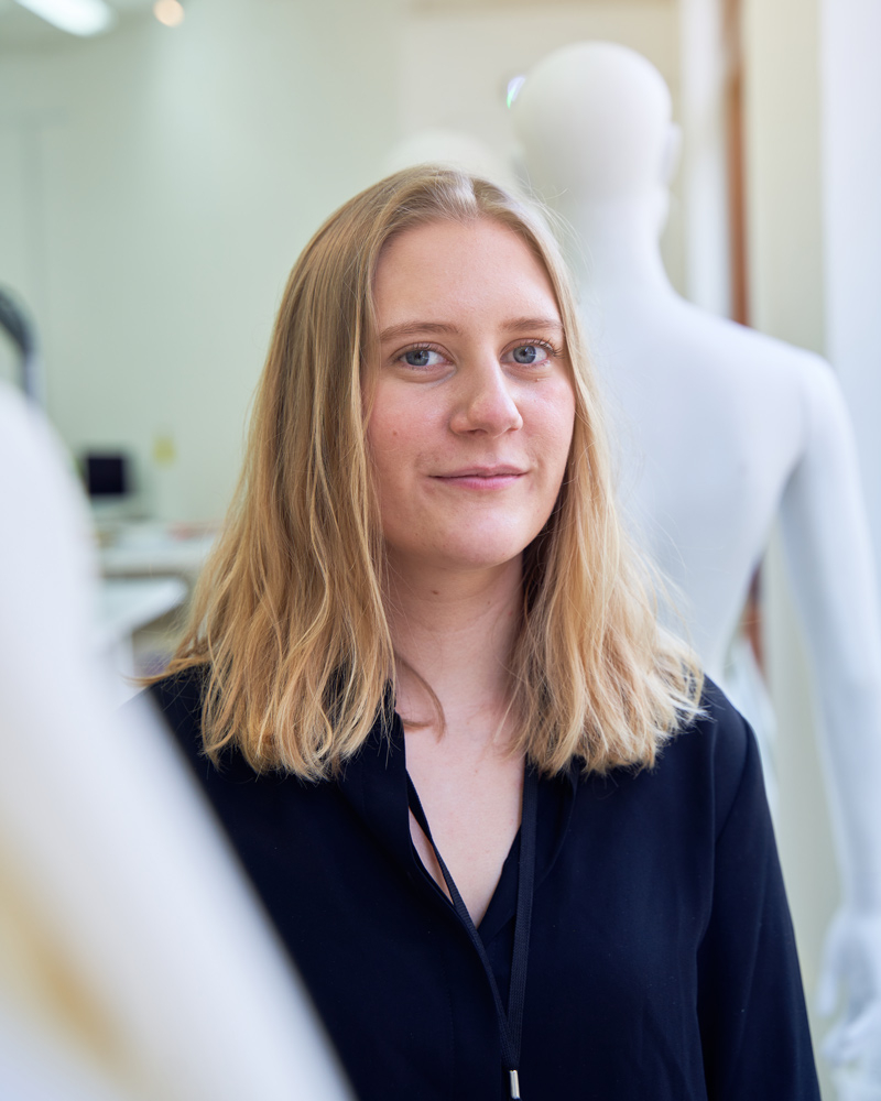 A young woman with dirty-blonde hair is standing amongst mannequins in the fashion studio, looking and smiling at camera