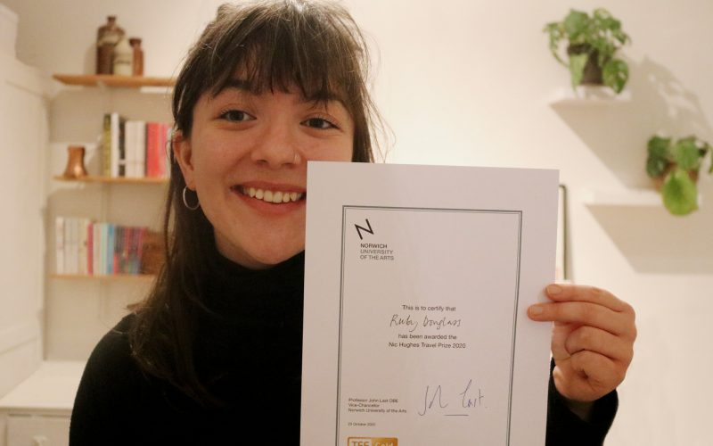 BA Graphic Communication student Ruby Douglass holds up her Nic Hughes Travel Prize 2020 certificate