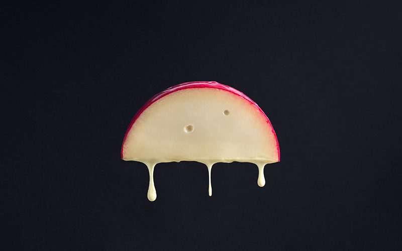 black background with wedge of cheese melting
