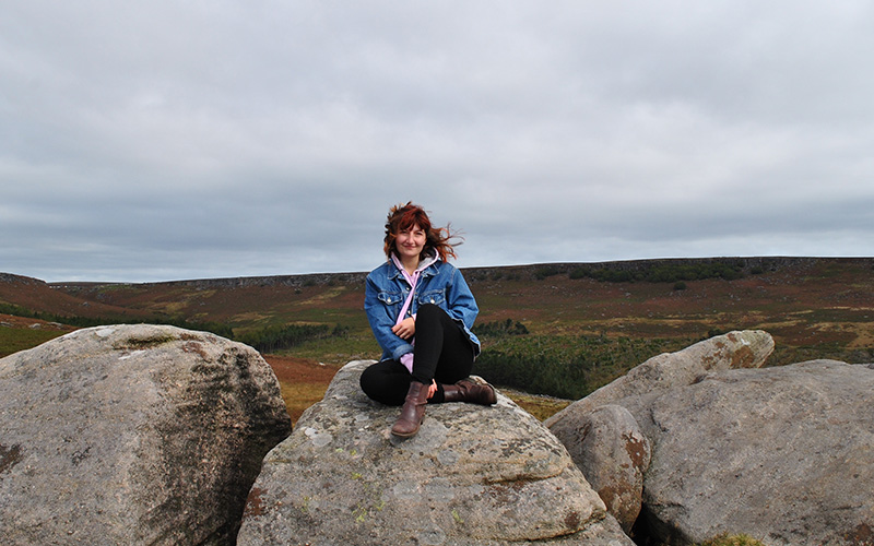 A young white woman in a denim jacket and black trousers sat on a large boulder outside against a grey sky