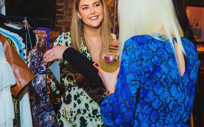 BA Fashion Communication and Promotion student Charlotte Lord talking to customers in front of a clothes rack at a bar event