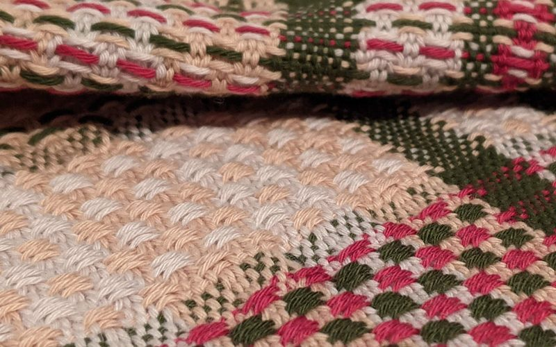 Close up photo of a weave, made from green, red, pale pink and neutral yarn