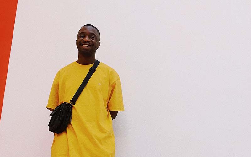 A young black man in a yellow t-shirt stood smiling against a white wall