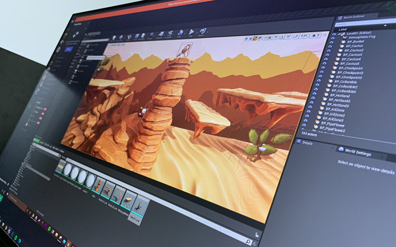 A computer monitor showed from the side with a game still of a desert on the screen