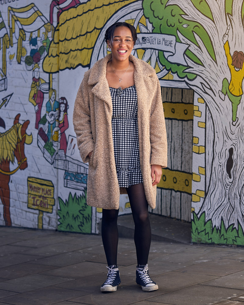 Person standing with cream wooly coat on infront of a mural