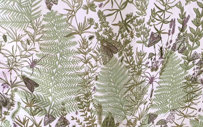 Detail of fabric showing a green print of fern leaves and insects on a white background