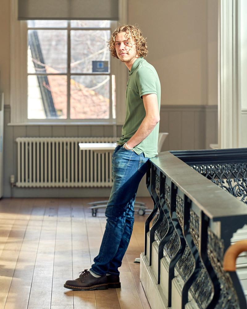 BA Architecture student Bradley Fletcher in the architecture studio, perching on the black railed balcony