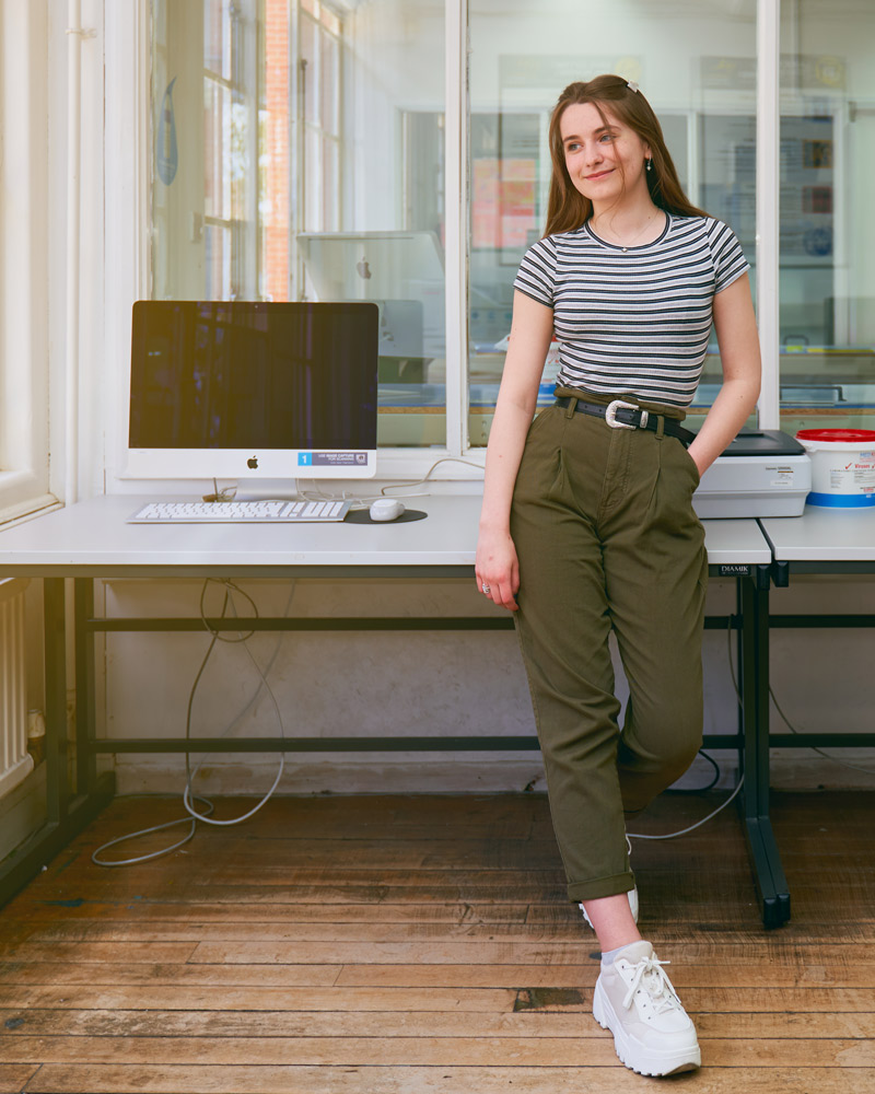 BA Design for Publishing student Sophie Ebbage in the digital design studio, perching on a desk next to an Apple iMac, looking out the window