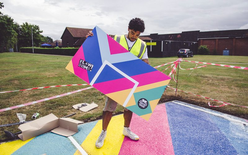 Graphic Design graduate Gareth Roberts standing on a painted basketball court, holding a multicoloured board in both hands whilst looking down at it