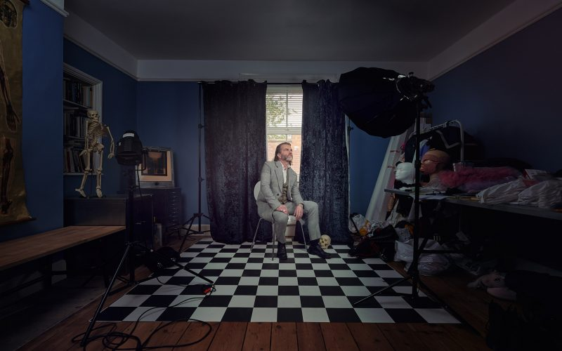 Person sitting in dark room with grey suit on standing on checkered flooring. There is a velvet blue curtain behind the person and blue walls in the room. To the left and right of the person there are lots of props such as masks, lights, a clothing rail and a skull.