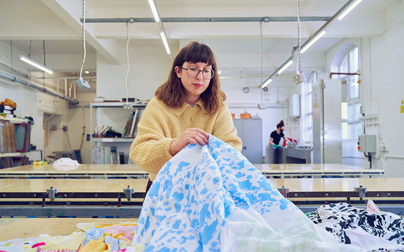 A woman with a yellow jumper and glasses holding a large pice of blue and white fabric