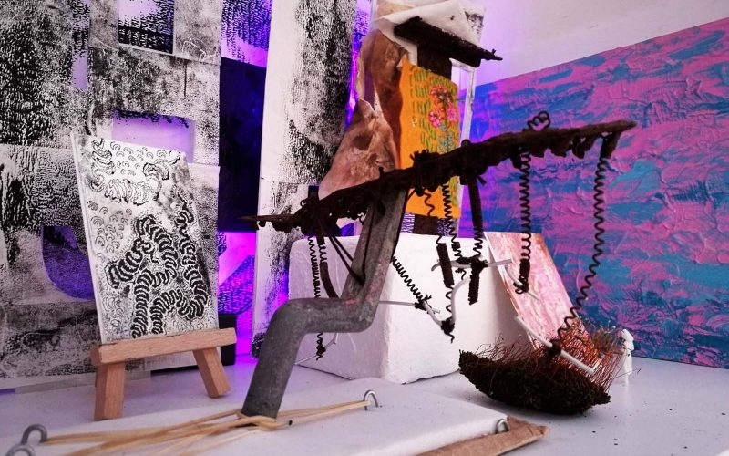 A mini wooden easel holding a black and white drawing surrounded by abstract objects and drawings