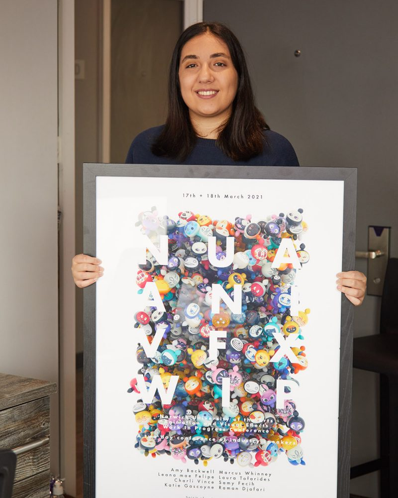 person holding a framed animation and vfx poster 2021