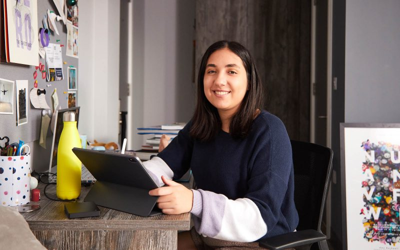 picture of person sitting at their desk with an iPad and apple pen smiling