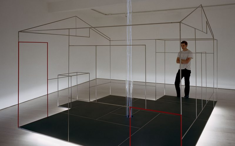 A person standing in Yuko Shiraishi's Space Elevator sculpture of a house