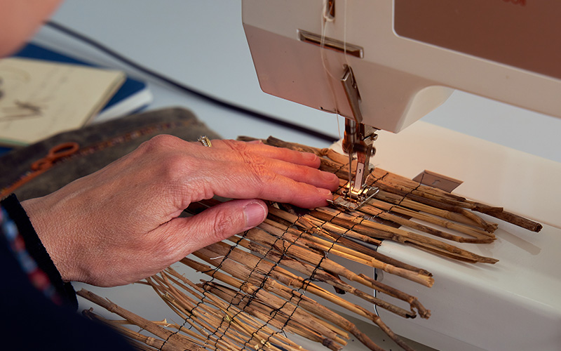 close up shot of a hand working on the sewing machine