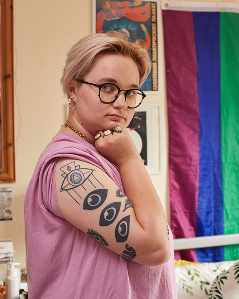 Person standing with tattoos on their arm, rainbow flag in background and they have blonde hair and glasses on