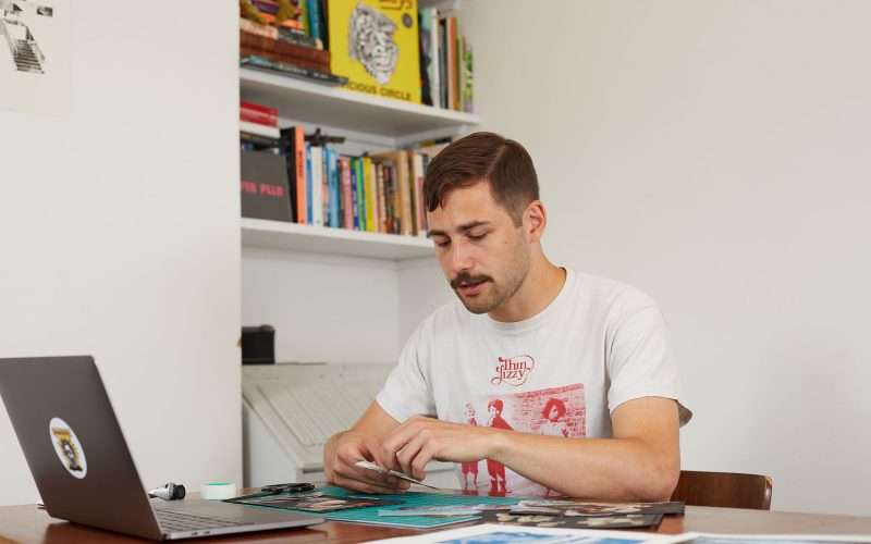 BA Illustration student Cal Hudson sits at their desk looking at their collage work