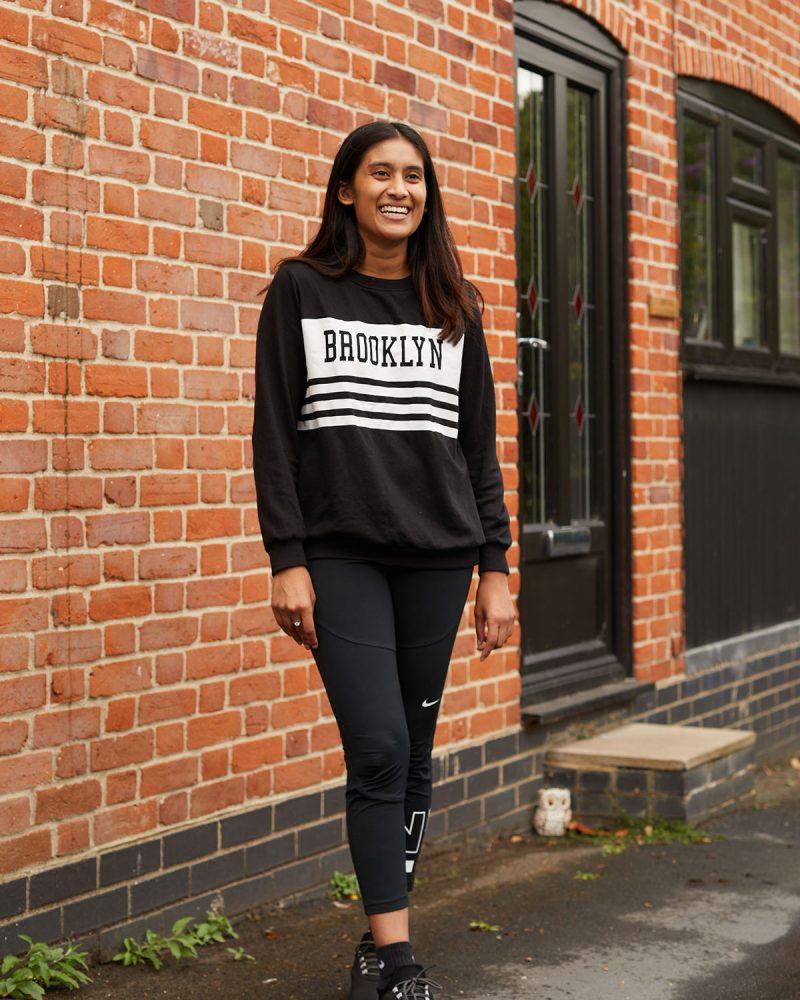BA Interior Design student Mahisha stood by a wall and a door