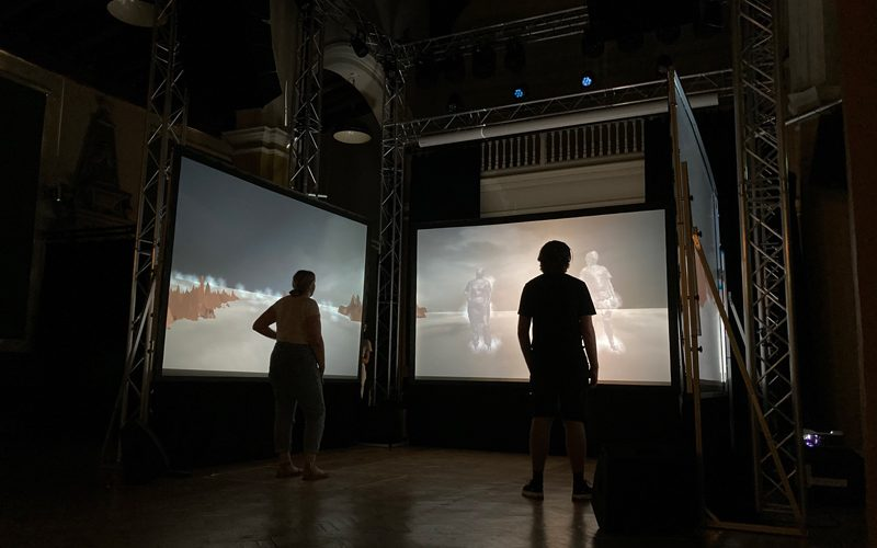 Two people standing in a dark room, in front of three screens with a projection of their bodies on