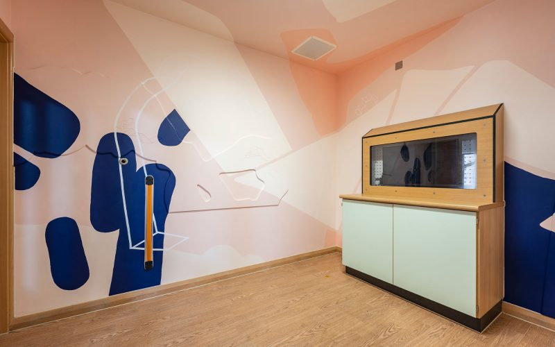 A hospital room at Northside House, Catton Ward showing bright blue and pink art works next to hospital equipment