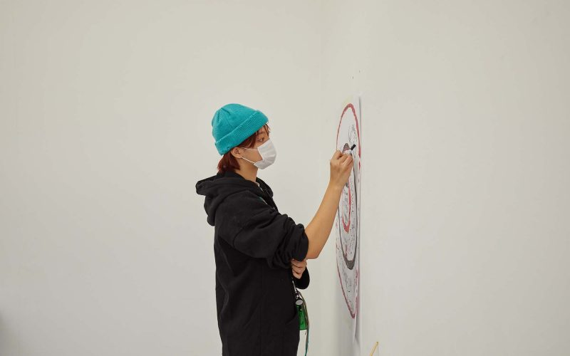 Student works on artwork on the wall in a hat and mask