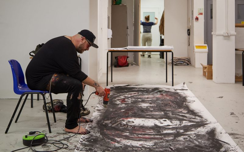 A student drying paint on a large mural, whilst sat on a chair