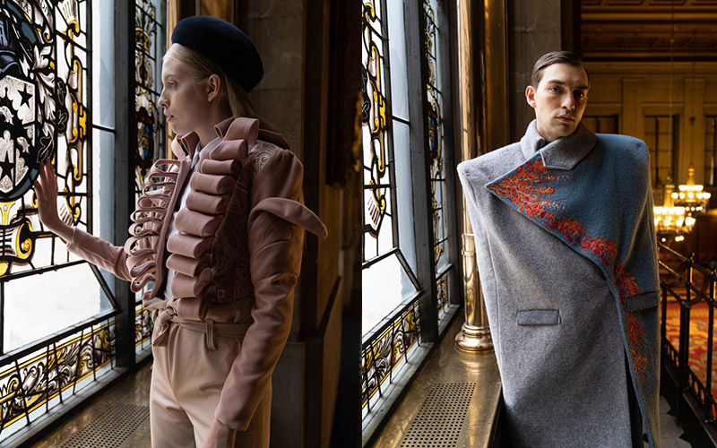 Two images of fashion models. On the left, a woman standing gazing out of a stained glass window, with her hand resting on it. She is wearing a pink tailored suit jacket with ruffles, and matching pink tailored trousers. On the right, a male model is facing camera, wearing a highly tailored grey armless coat. One half of the coat's lapel is in blue with orange pattern around the edge.
